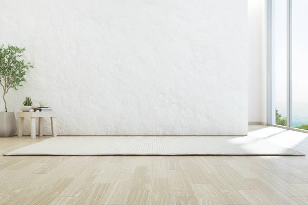 海景起居室的豪華夏日沙灘屋內有玻璃窗和木地板。空粗糙的白色混凝土牆背景在假期家庭或度假別墅。 - 無人 個照片及圖片檔