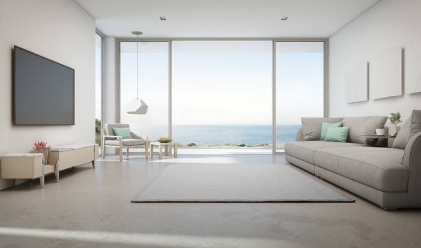 Sea view living room of luxury summer beach house with large glass door and wooden terrace. TV on white wall against big gray sofa in vacation home or holiday villa. 3d rendering of hotel interior. coastal feature stock pictures, royalty-free photos & images