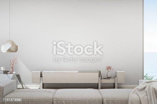 istock Sea view living room of luxury summer beach house with TV stand and wooden cabinet. Empty white concrete wall background in vacation home or holiday villa. 1131373392