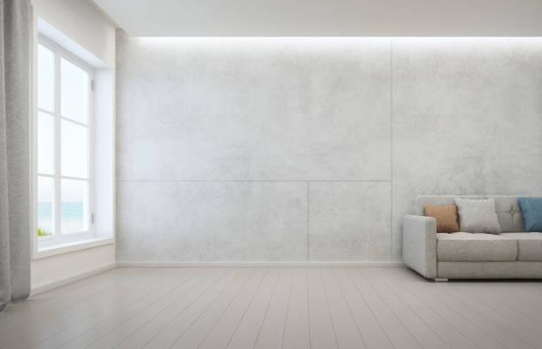 wohnzimmer mit parkettboden und betonwand hintergrund in modernen strandhaus, weißen inneren des ferienhauses mit meerblick - betonboden wohnzimmer stock-fotos und bilder