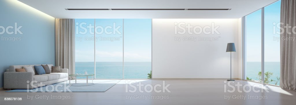Sea view living room with wooden floor and empty white wall background in luxury beach house, Modern interior of vacation home stock photo