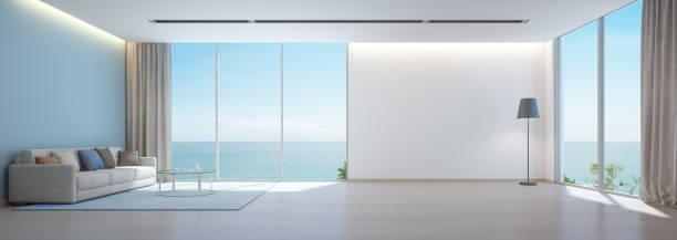 Sala de estar com piso de madeira e fundo de parede branca vazia com vista mar na casa de praia de luxo, interior moderno de casa de férias - foto de acervo