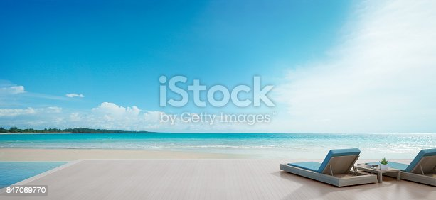 istock Sea view swimming pool beside terrace and beds in modern luxury beach house with blue sky background, Lounge chairs on wooden deck at vacation home or hotel 847069770