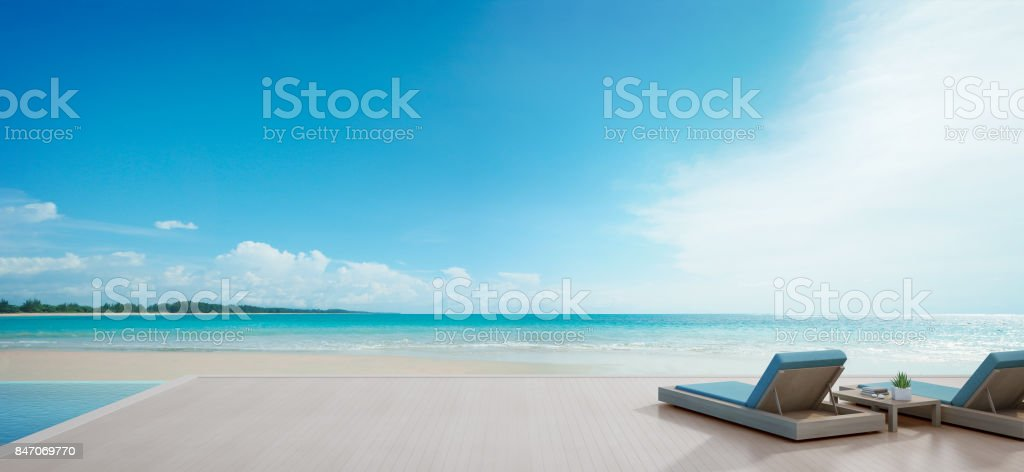 Sea view swimming pool beside terrace and beds in modern luxury beach house with blue sky background, Lounge chairs on wooden deck at vacation home or hotel stock photo