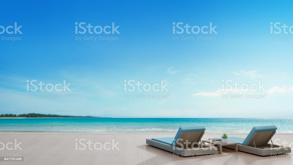 Sea view terrace and beds in modern luxury beach house with blue sky background, Lounge chairs on wooden deck at vacation home or hotel stock photo