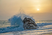 Sea wave beating with force against the rock at sunset