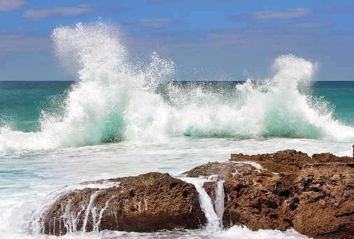 sea wave crashing on rocks
