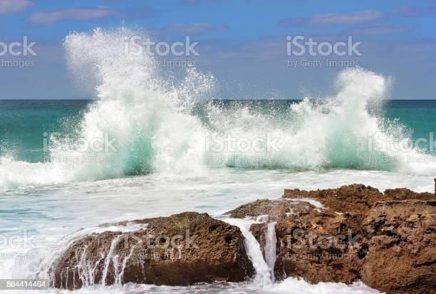 Photo of sea wave crashing on rocks