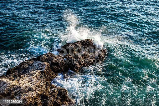 A sea wave breaking upon a rock.