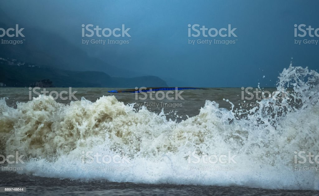 Sea wave in stormy weather. The turbid wave. Low clouds over the coast. Montenegrin beach in rainy weather. Montenegro. stock photo