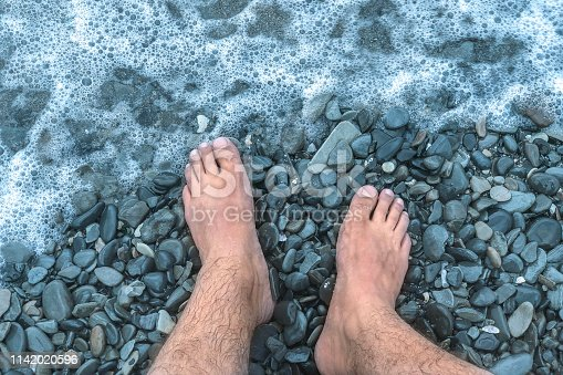 istock A sea wave on a stone beach covers the rocks, male feet in the splashing wave. Close up, outdoors, copy space. 1142020596