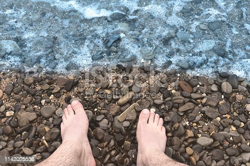 istock A sea wave on a stone beach covers the rocks, male feet in the splashing wave. Close up, outdoors, copy space. 1142025536
