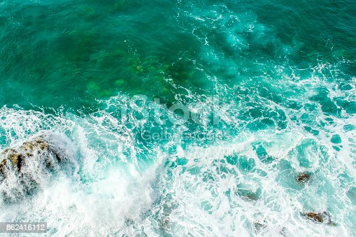 istock Sea waves break up on the stones of the coast. The raging sea and foam. View from above. Green background. 862416112