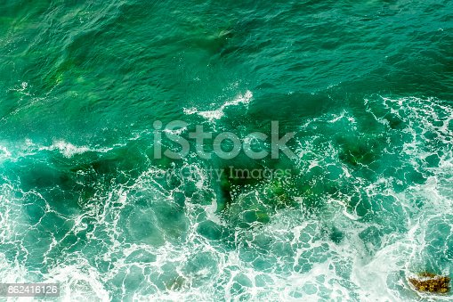 istock Sea waves break up on the stones of the coast. The raging sea and foam. View from above. Green background. 862416126
