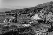 Crashing waves of water on the granite coastline of Garrapata State Park in California's Central Coast in black and white.