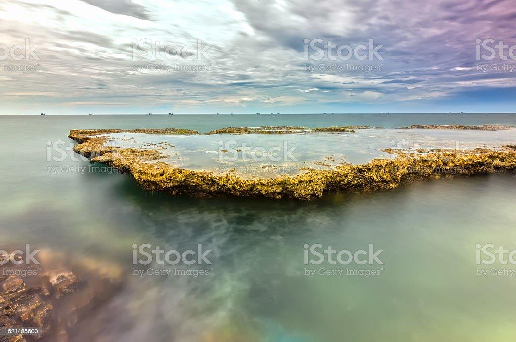 Sea waves crashing on plates sea rocks creating waterfalls foto stock royalty-free