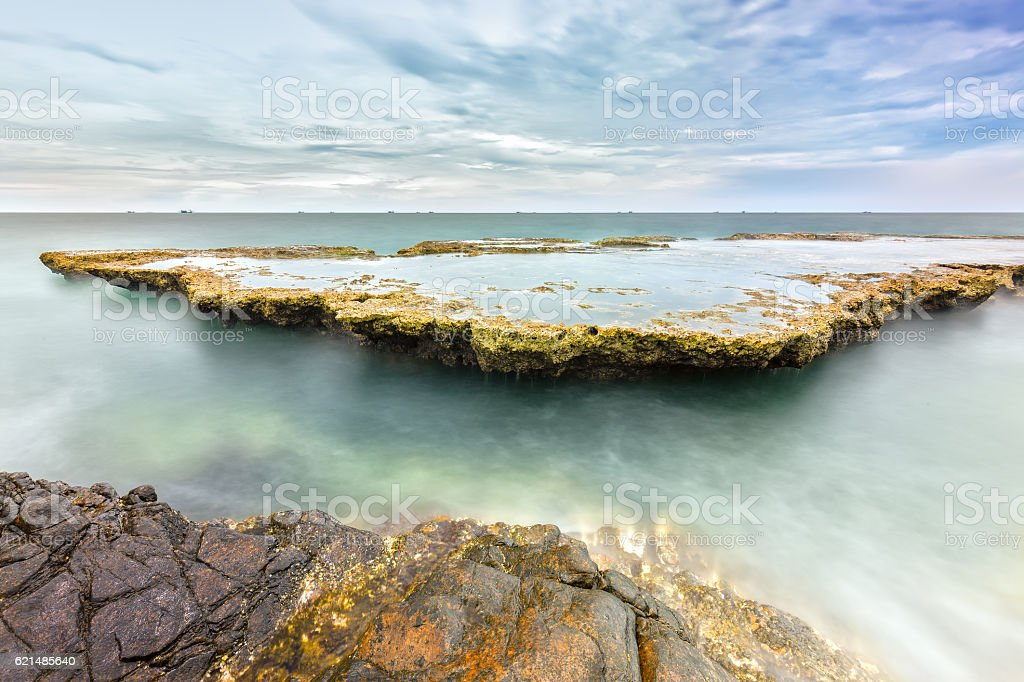 Sea waves crashing on plates sea rocks creating waterfalls Lizenzfreies stock-foto