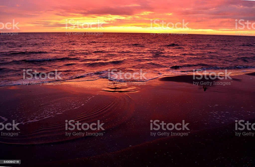 Sea waves during a colorful sunset over a romantic beach stock photo