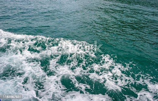 843079528istockphoto Sea waves hit the beautiful emerald green sea boat. 1183567631