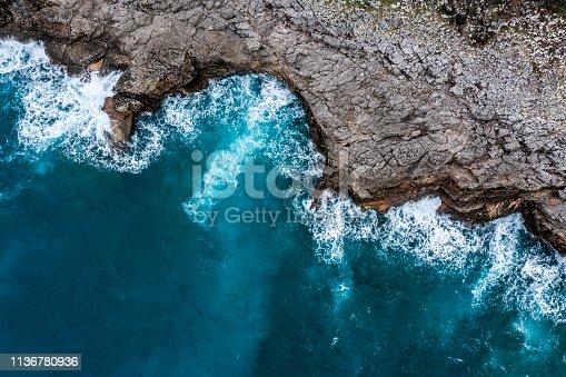 999001484 istock photo Sea waves hitting the rocky shore 1136780936