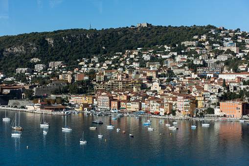 Blue sea with small luxury yachts and boats with cute village on a hill at background on sunny summer day. Aerial view of Mediterranean sea in french riviera. High quality photo