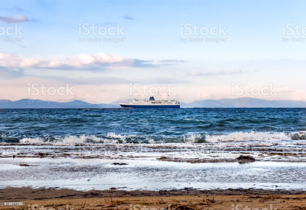 Sea with waves and a large blue-white ferry ship leaving port of Rafina on a winter day. stock photo