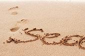 Sea handwritten on the sand footprint on background