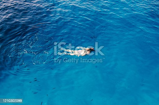 Woman snorkeling in deep blue sea water. High Above view