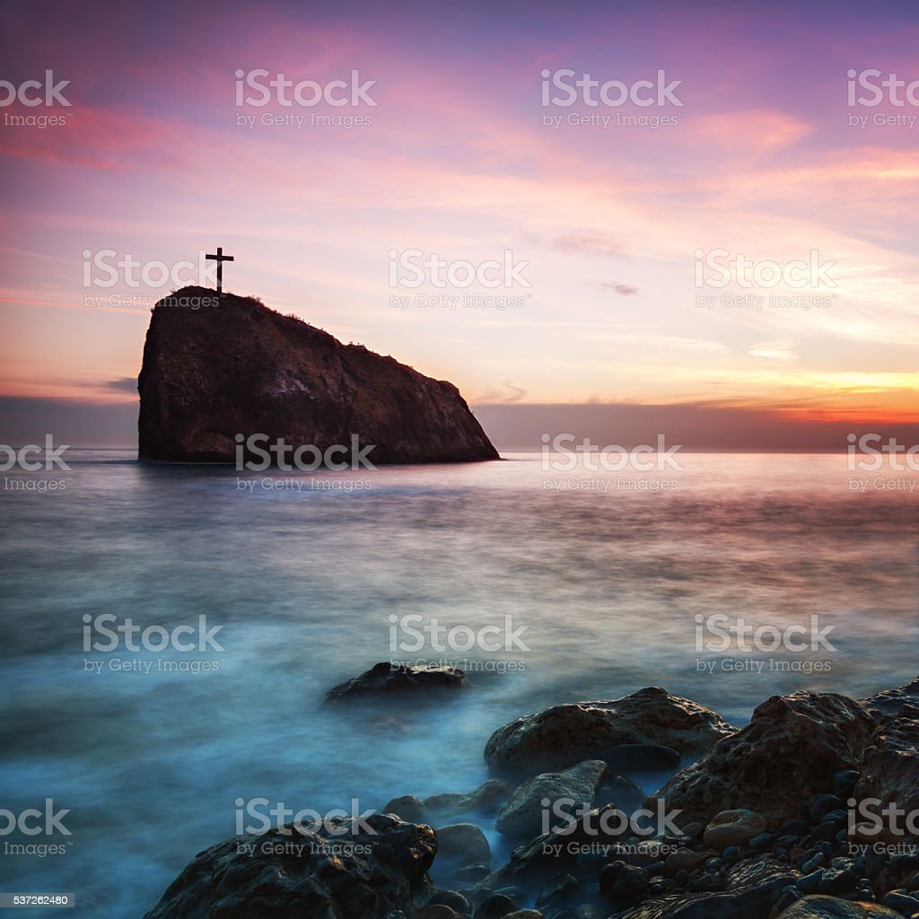 Seacoast at sunset and cross on a rock stock photo
