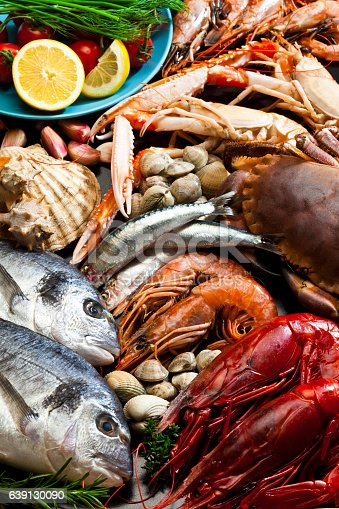 High angle view of a large group of seafood like fish, crustacean and mollusk. The composition includes two sea bream, giant red shrimp, prawn, crab, clam and scallop. DSRL studio photo taken with Canon EOS 5D Mk II and Canon EF 100mm f/2.8L Macro IS USM