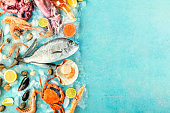 Seafood banner with a place for text. Fish, shrimps, crab, scallops, shot from above on a blue background with a place for text