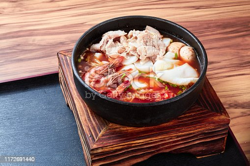 istock Seafood beef udon noodles in a black China bowl on a log table 1172691440