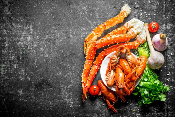 zeevruchten. gekookte rivierkreeft en krab met knoflook, peterselie en tomaten. - krab gerecht stockfoto's en -beelden