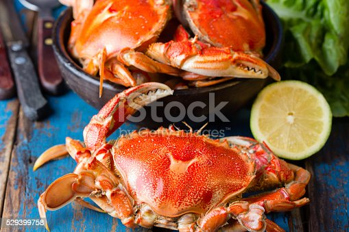 Seafood. Crabs in clay bowl and clams soup on wooden blue background