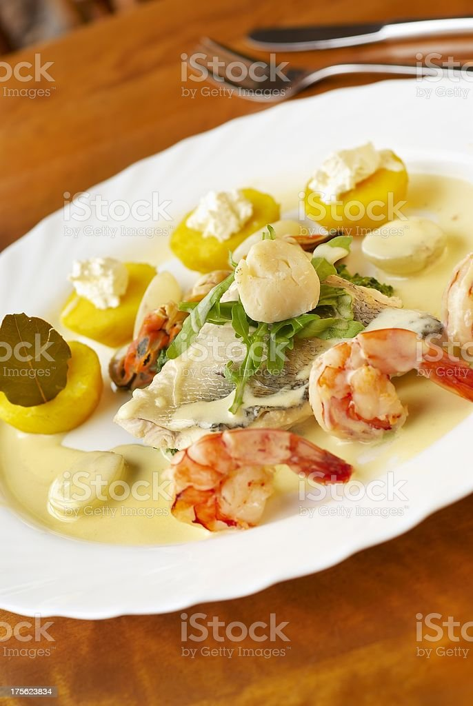 Seafood dish with spinach, yellow potatoes and cream sauce royalty-free stock photo