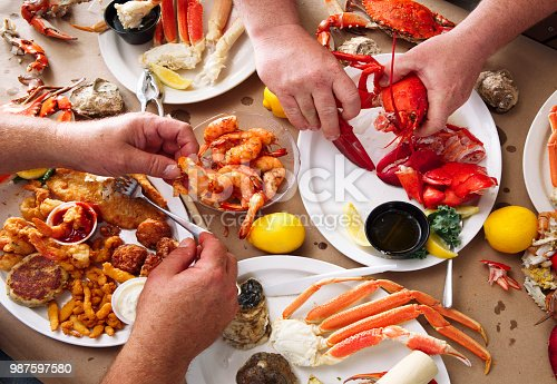 Overhead view of two men eating at a seafood feast