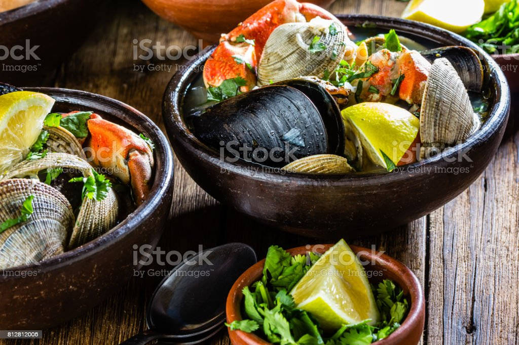 Seafood mussels, clams and crabs soup. Mariscal or paila marina served in clay plates stock photo