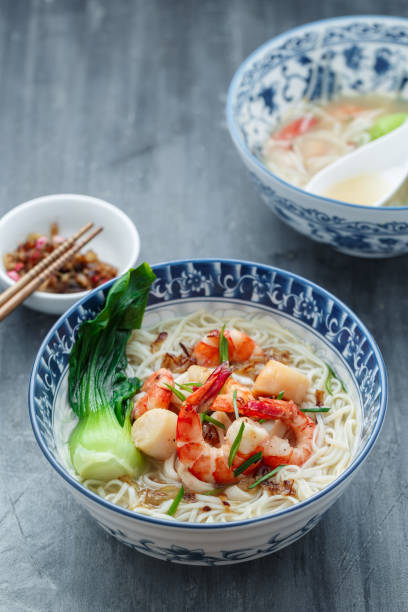 Seafood noodle soup or singaporean bee hoon in traditional bowl stock photo