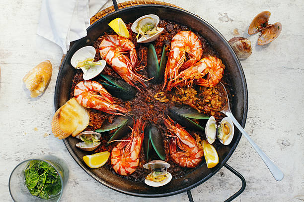 seafood paella - paella stock photos and pictures