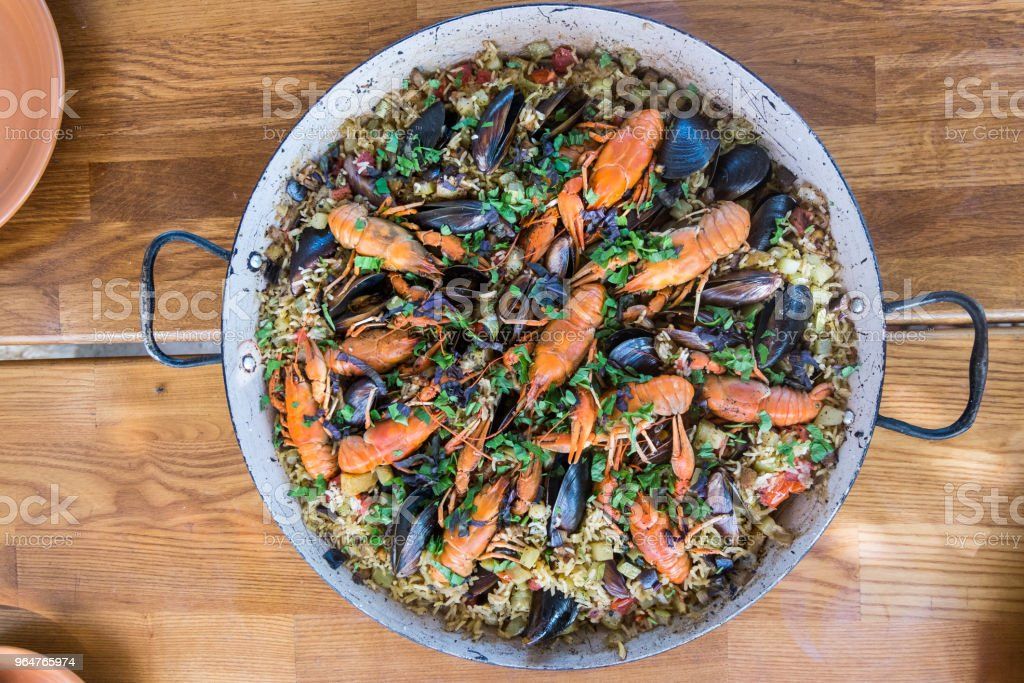 Seafood paella with mussels and crayfish on wood table royalty-free stock photo