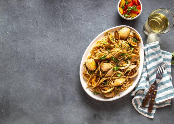skaldjur pasta. italienska spaghetti alle vongole. musslor spaghetti på vit tallrik med vitt vin, grå bakgrund. topp-vy - pasta vongole bildbanksfoton och bilder