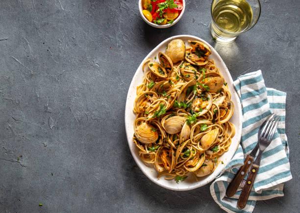skaldjurs pasta. italienska spaghetti alle vongole. musslor spaghetti på vit tallrik med vitt vin, grå bakgrund. uppifrån och - pasta vongole bildbanksfoton och bilder