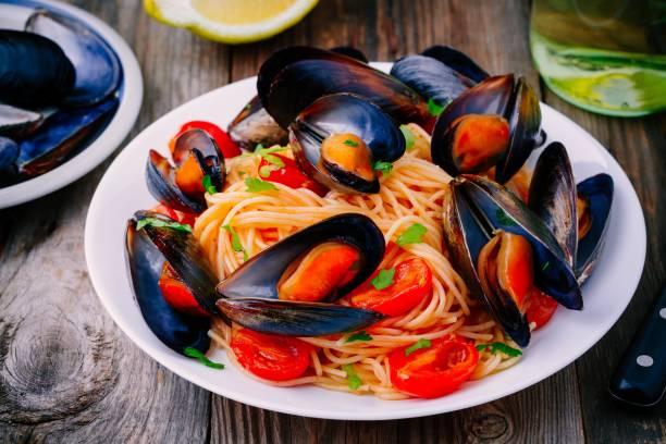 fisk och skaldjur pasta spaghetti med musslor och tomater - pasta vongole bildbanksfoton och bilder