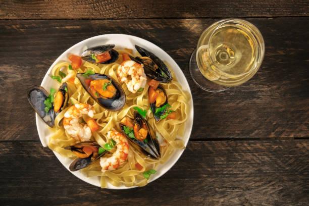 pasta mit meeresfrüchten mit muscheln, garnelen und weißwein - weinsoße stock-fotos und bilder