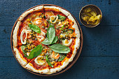 Pizza with shrimps, squids, scallops, mussels and capers