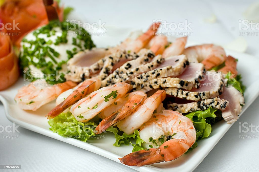 Seafood plate with shrimp and seared tuna on white platter stock photo