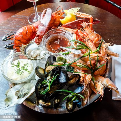 fresh seafood platter with red lobster, langoustine, prawns, mussels, oysters, clams, with a tartare and sweet chilli sauce on a wooden background