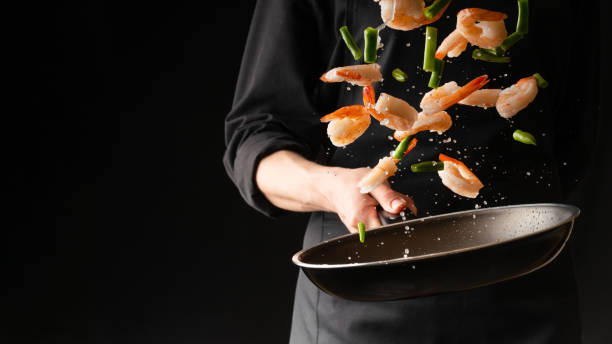 seafood, professional cook prepares shrimps with sprigg beans. cooking seafood, healthy vegetarian food and food on a dark background. horizontal view. eastern kitchen - chef zdjęcia i obrazy z banku zdjęć
