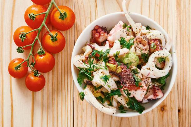 Seafood salad in white bowl on wooden table Seafood salad in white bowl on wooden table cuttlefish stock pictures, royalty-free photos & images