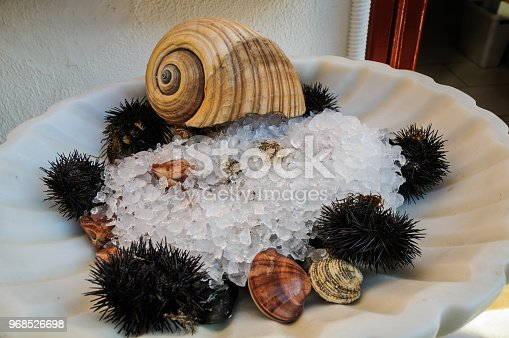 A tray outside a Mykonos restaurant  holds fresh  sea urchins, clams and sea snails on a bed of ice